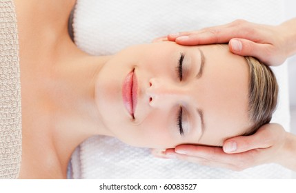 Young relaxed woman receiving a head massage in a spa centre