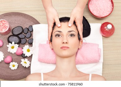 young relaxed woman receiving a head massage at spa center