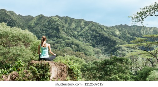 Young relaxed woman sitting in a beautiful mountain setting. People zen serenity in nature.
