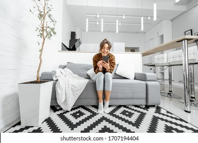 Young relaxed woman sitting with mobile phone on the couch at the living room at home, wide view on the modern white interior