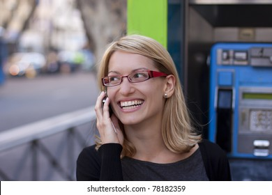 Young relaxed woman talking on the cell phone with the retro phone boot in the background.