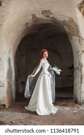 Young renaissance redhead ghost princess with hairstyle in old castle. Doll in the corset. Victorian princess in palace. Fabulous rococo ghost in white dress against the backdrop of old stone wall.