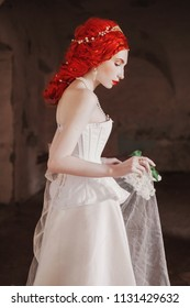 Young renaissance redhead princess with hairstyle in the old castle. Fabulous rococo queen in white dress against the backdrop of old stone wall. Doll in the corset. Victorian princess in palace;