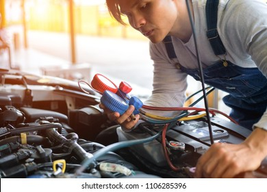 young repairman check the pressure and leak , repair of air conditioning. for use on air condition systems in car