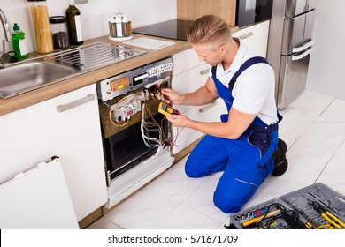 Young Repairman Checking Dishwasher With Digital Multimeter