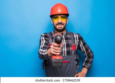Young repairman with drill perforator isolated on blue