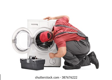 Young repairman examining a washing machine and holding a wrench isolated on white background