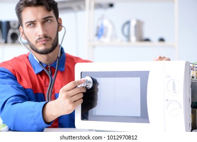 Young repairman fixing and repairing microwave oven