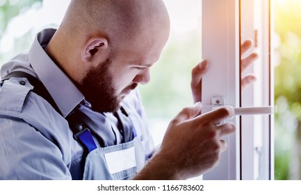 Young repairman fixing window frame in room at daytime