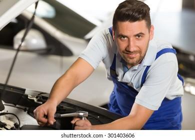 Young repairman posing at camera in repair shop.