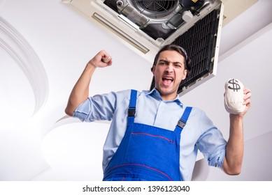 Young repairman repairing ceiling air conditioning unit