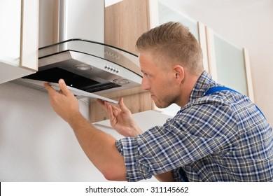 Young Repairman Repairing Kitchen Extractor Filter In Kitchen Room