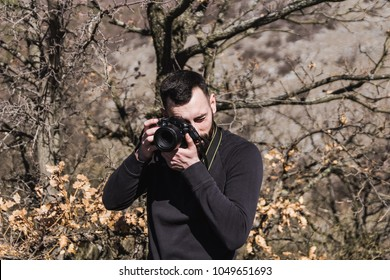 The young researcher investigating nature. Fieldwork biologist. Biologist photographing in nature. A man photographing a sunny day in nature. Young mixed race male photograp
