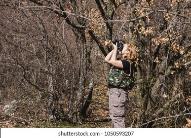 The young researcher investigating nature. Fieldwork biologist. Photographing in nature. Sunny day for photography. A girl photographing a sunny day in nature. Young mixed race female photog