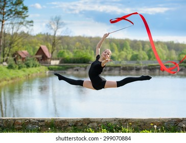 Young rhythmic gymnast doing split jump during ribbon exercises.