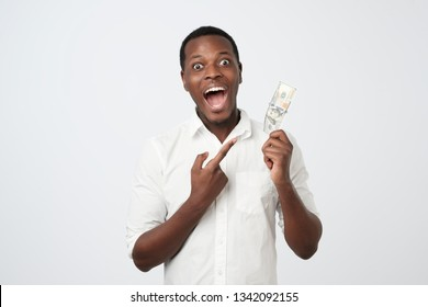 Young rich african american man in shirt holding one hundred dollar with surprise isolated over white wall