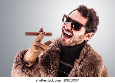 a young and rich man wearing a sheepskin coat isolated over a white background holding a cigar
