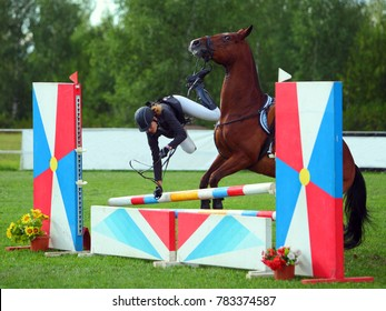 Young rider falling from horse during a competition