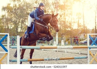 Young rider girl at show jumping. Horse rider jumps over hurdle