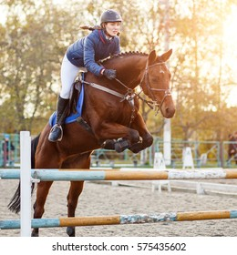 Young rider girl at show jumping. Horserider jumps over hurdle