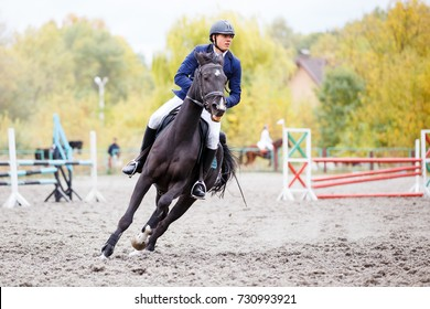 Young rider man on bay horse galloping on his course at show jumping competition