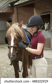 Young rider preparing a pony for her riding lesson - September 2016 - Teenager adjusting the bridle