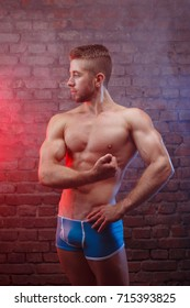 Young ripped man bodybuilder with perfect abs, shoulders,biceps, triceps and chest posing on brick wall background