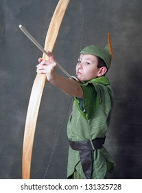 Young Robin Hood drawing a bow and arrow