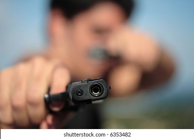 A young, robust man, in his 20's with dark hair pointing 2 pistols to the camera.
