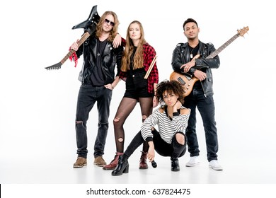 Young rock and roll band standing with microphone, drumsticks and guitars isolated on white
