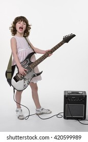 Young rocker gets crazy while playing the electric guitar connected to its amp for making the sound louder. Opened mouth and mad eyes is the combination for a true hardcore.