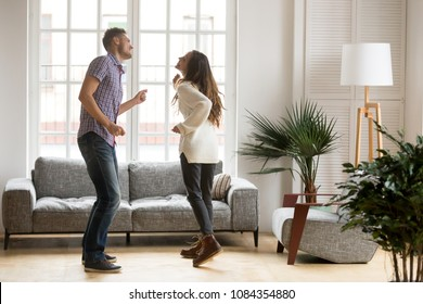 Young romantic carefree couple in love dancing spending time together at home, cheerful smiling man and woman having fun in cozy modern living room, happy husband and wife enjoying weekend