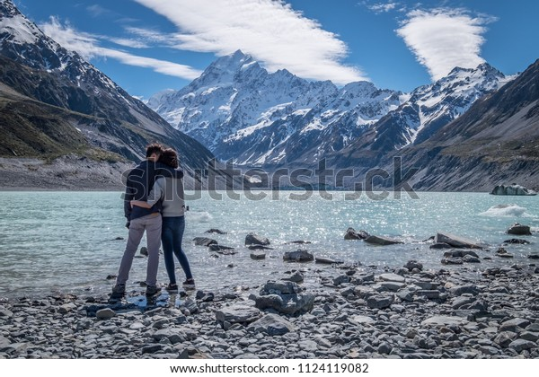 A young romantic couple admiring the beautiful scenery of mount cook in New Zealand. The rocky shore, stunning snow mountain and the clear sky create a perfect background or wallpaper.
