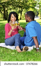 Young romantic couple celebrating with wine in summer park