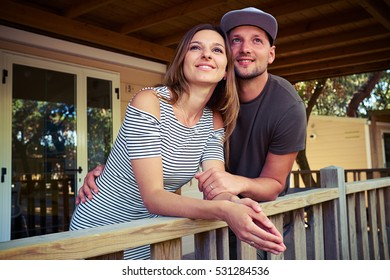Young romantic couple dreaming and looking up while standing on the terrace. Thoughtful couple hugging. Spending time together