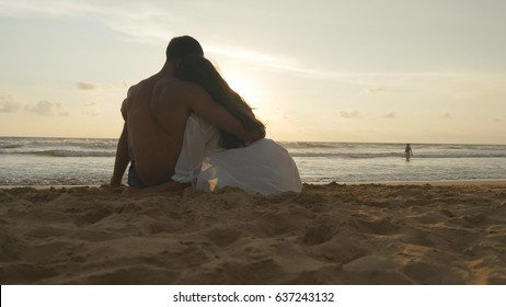Young romantic couple is enjoying beautiful sunset sitting on the beach and hugging. A woman and a man sits together in the sand on the sea shore, admiring the ocean and landscapes. Close up.