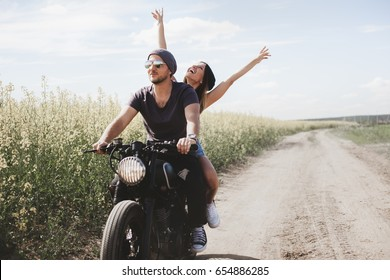 Young romantic couple in a field on a motorcycle. Love, freedom, togetherness concept. Happy guy and girl travel on a motorbike