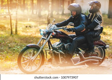 Young romantic couple in a forest road on a motorcycle. Love, freedom, togetherness concept. Happy guy and girl travel on a motorbike, road trip adventure concept