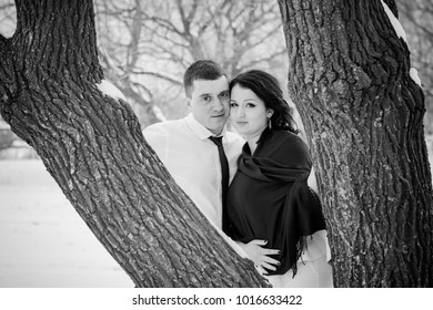 Young romantic couple is having fun outdoors in winter park, lovers are hugging and kissing in Saint Valentine's Day.