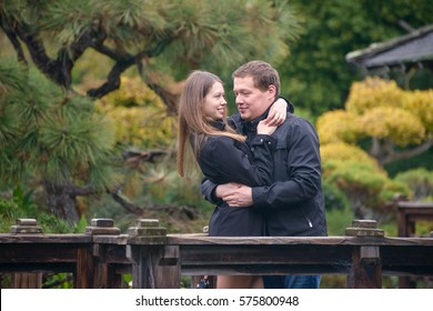 Young romantic couple hugging on the bridge in Japanese garden