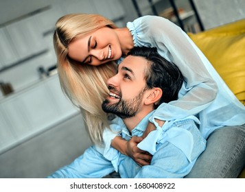 Young romantic couple hugging and smiling while sitting in the bedroom.  Loving everything about her.