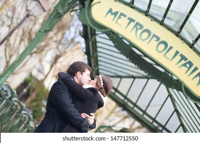 Young romantic couple kissing near metro station in Paris