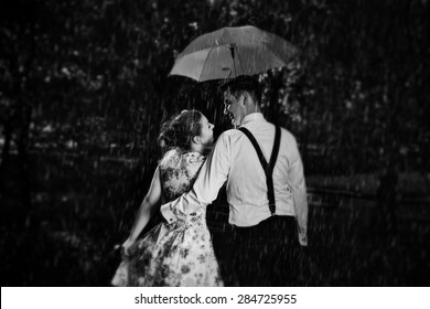Young romantic couple in love flirting in rain, man holding umbrella. Dating, romance, black and white