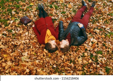 Young romantic couple in love woman and man in casual warm clothes holding hands looking at each other lying on fallen leaves in autumn city park outdoors. Love relationship family lifestyle concept
