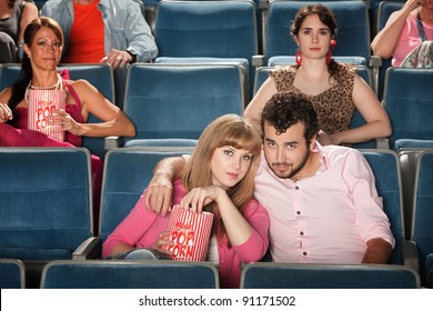 Young romantic couple with popcorn bag at movie in theater
