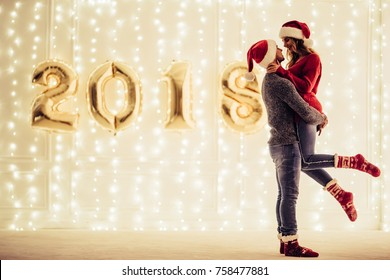 Young romantic couple in Santa Claus hats is waiting for Christmas at home together. Hugging and kissing in New Year Eve on the background of garlands and letters 2018.