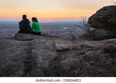 Young romantic couple sitting on mountain cliff looking to stunning panorama over small town Vrsac in sunset.