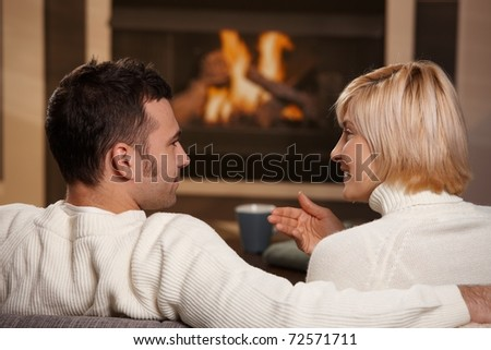 Young romantic couple sitting on sofa in front of fireplace at home, looking at each other, talking, rear view.?