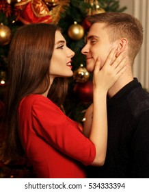 Young romantic couple standing and hugging in christmas decorated home interior. Pretty woman in red dress and man in black