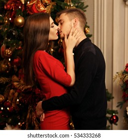 Young romantic couple standing and kissing in christmas decorated home interior. Pretty woman in red dress and man in black